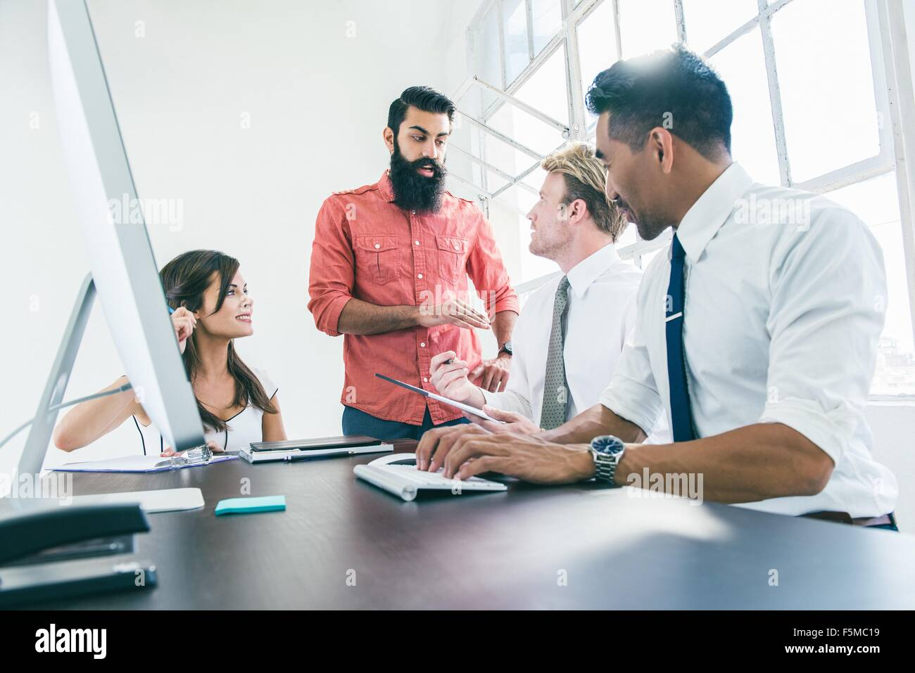 Business people in brainstorming meeting by office window - Stock Image