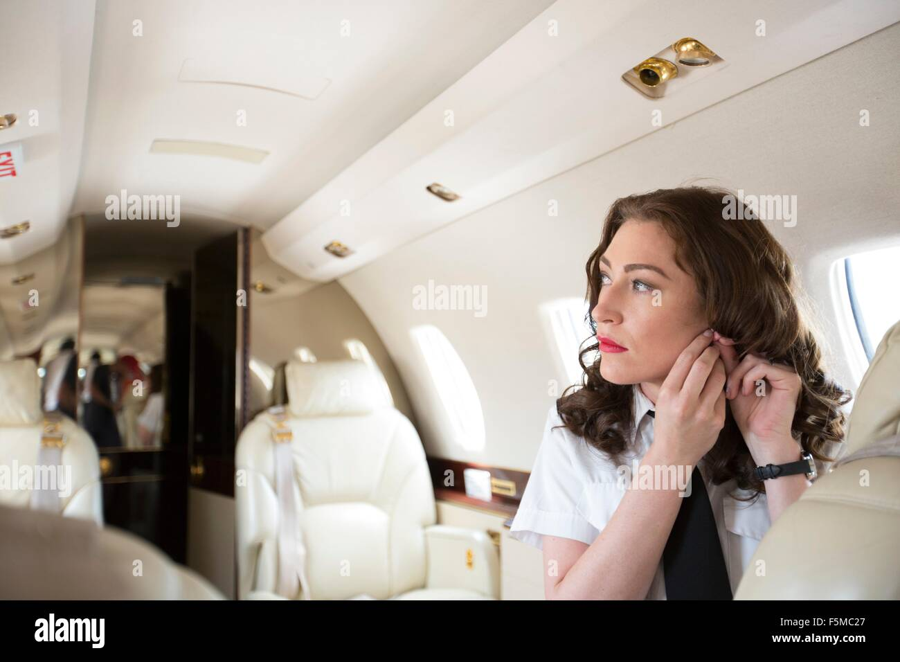 Female flight attendant putting on earring in cabin of private jet - Stock Image