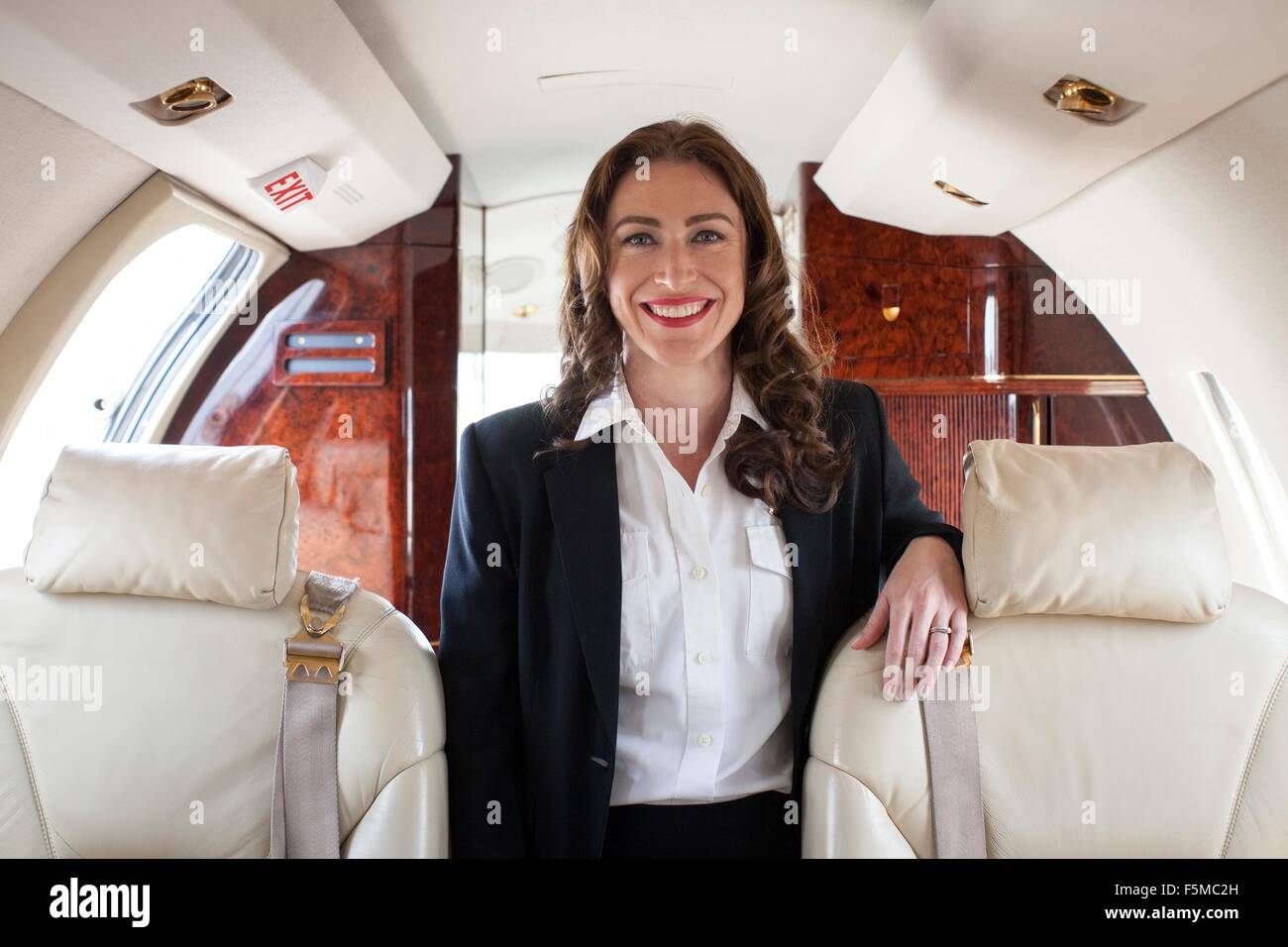 Portrait of female flight attendant on private jet - Stock Image