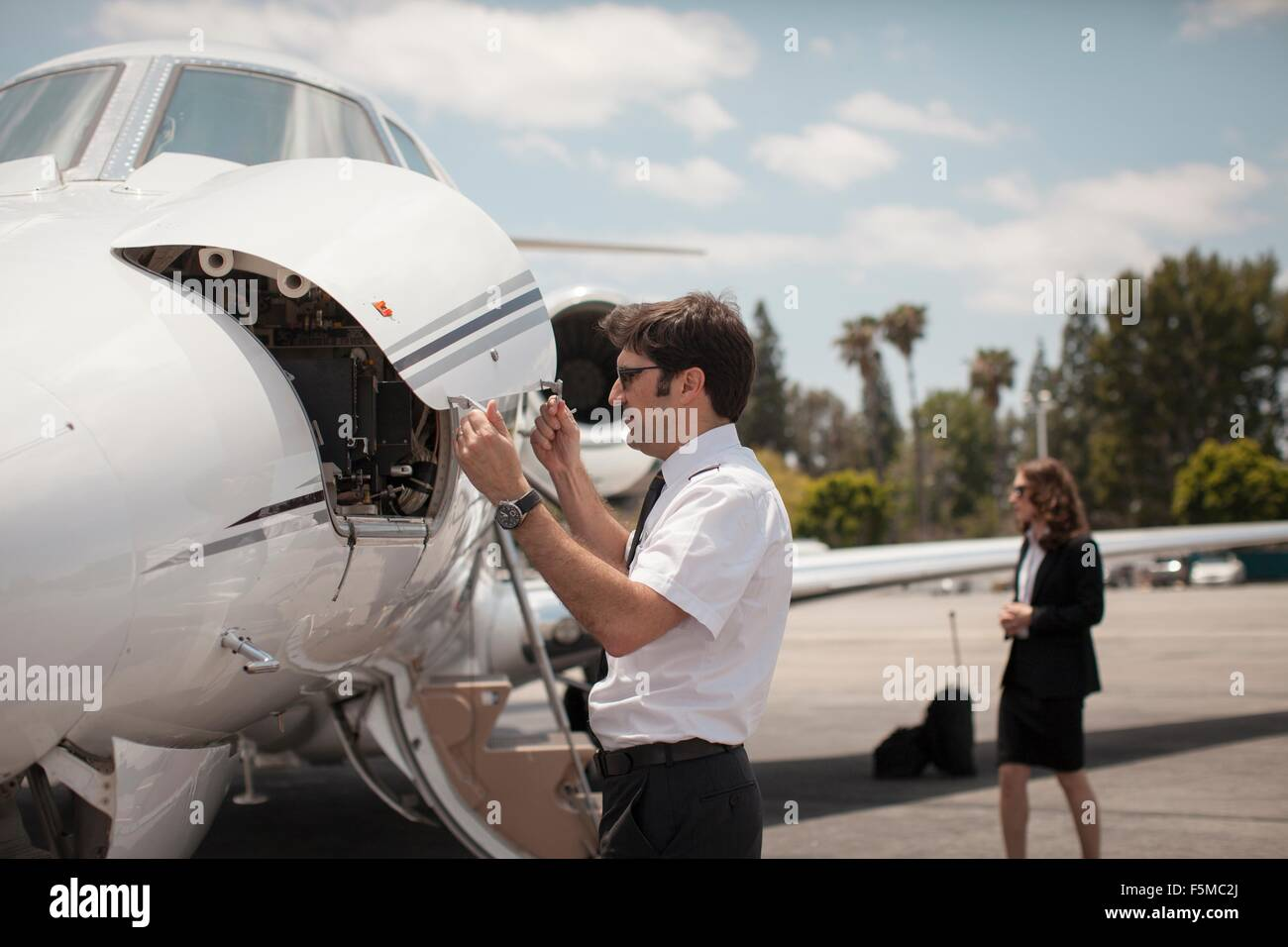 Male pilot checking private jet at airport - Stock Image