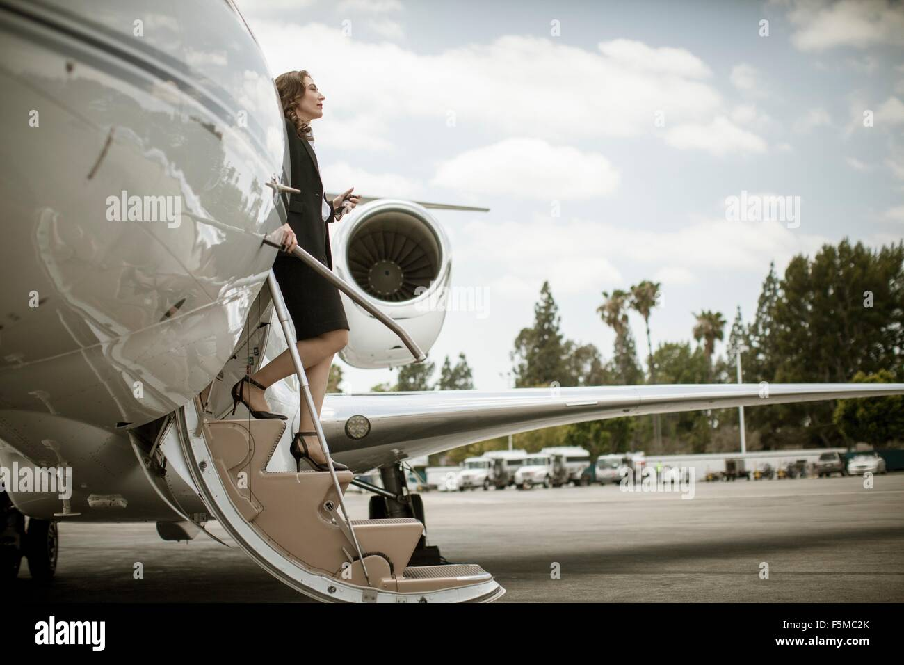 Female businesswoman stepping from private jet at airport - Stock Image