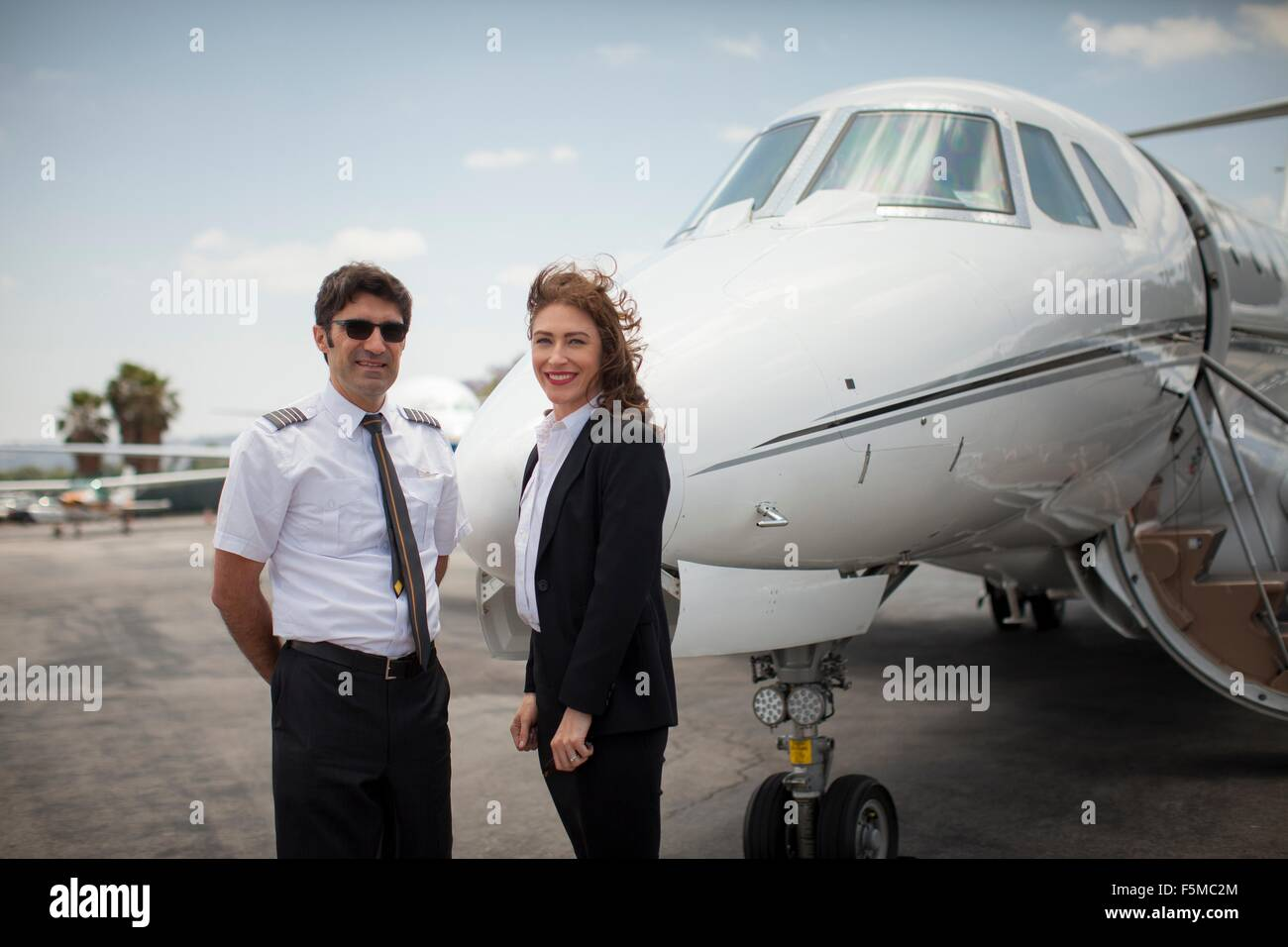 Portrait of female businesswoman and pilot of private jet at airport - Stock Image