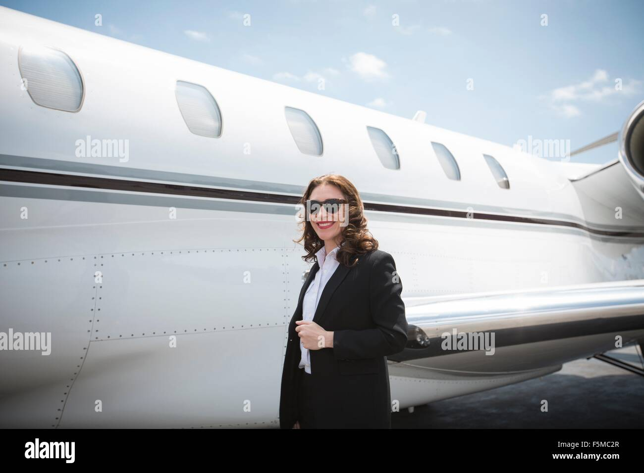 Portrait of female businesswoman and private jet at airport - Stock Image