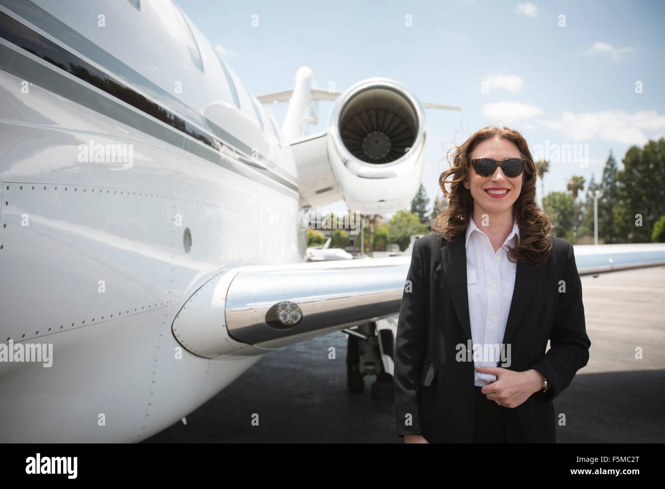 Portrait of mid adult female businesswoman and private jet at airport - Stock Image