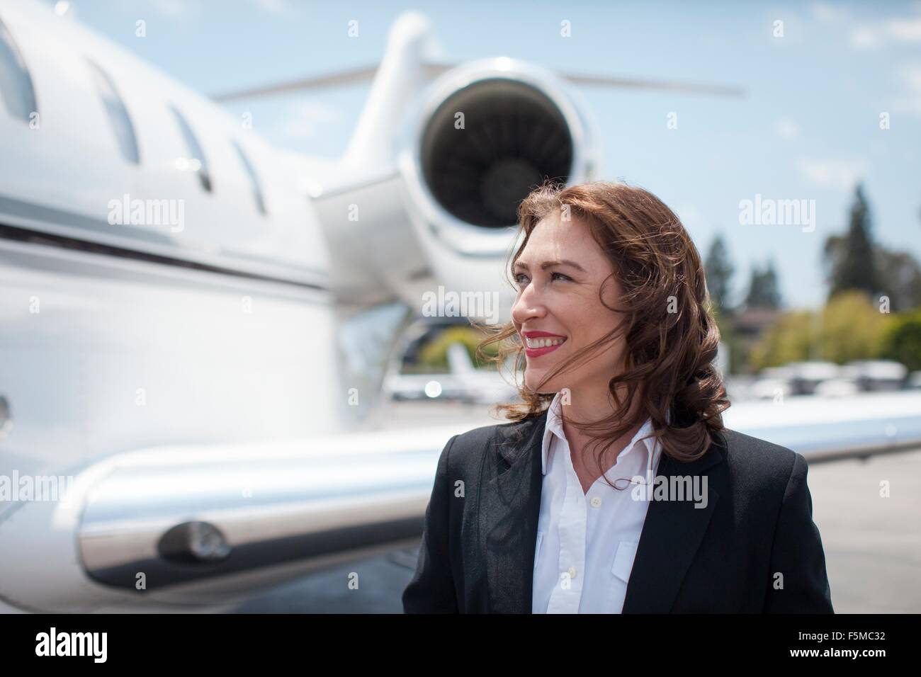 Mid adult female businesswoman and private jet at airport - Stock Image