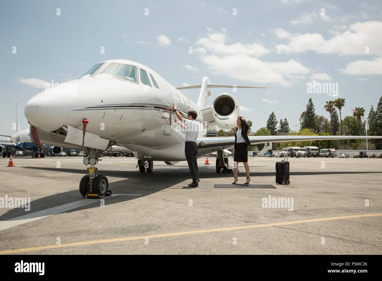 Female businesswoman preparing to  travel in private jet at airport - Stock Image