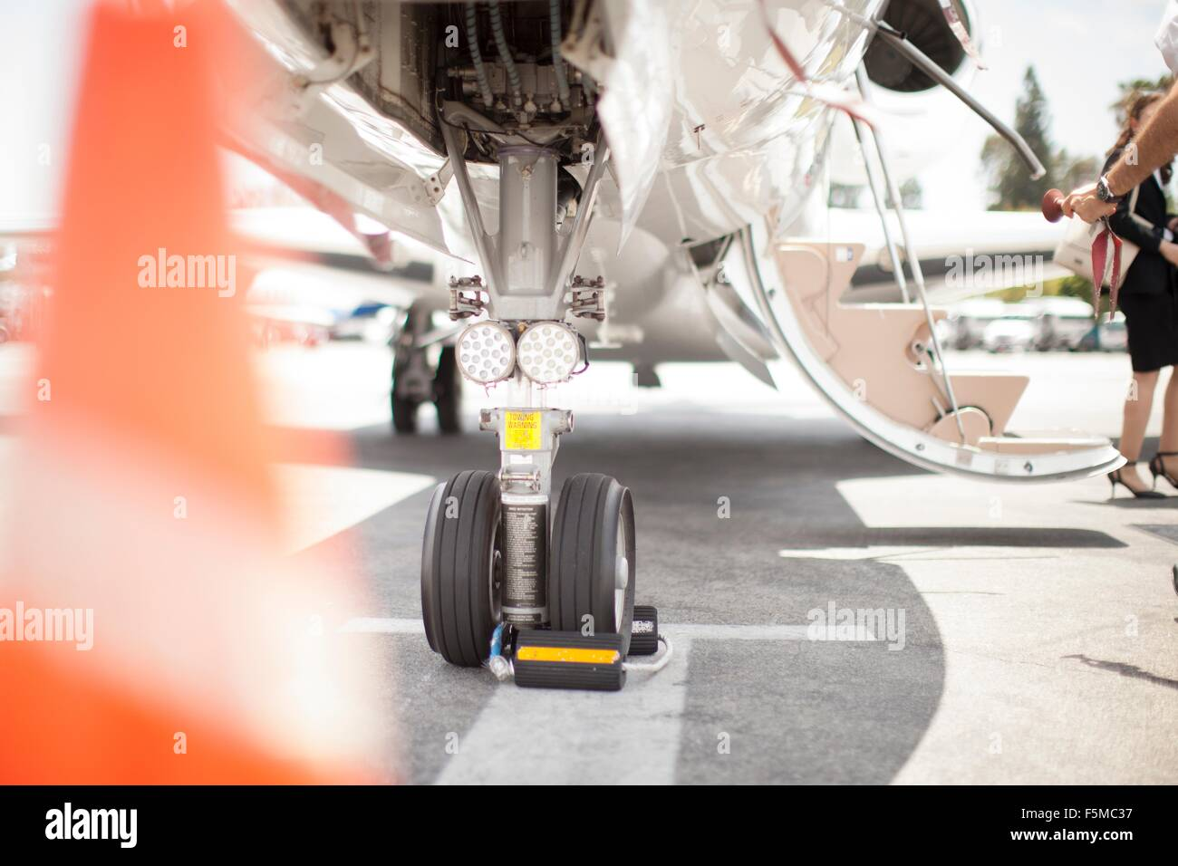 Female businesswoman leaving private jet at airport - Stock Image