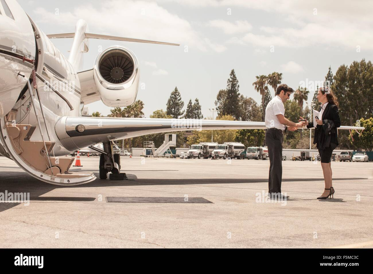 Female businesswoman shaking hands with private jet pilot at airport - Stock Image