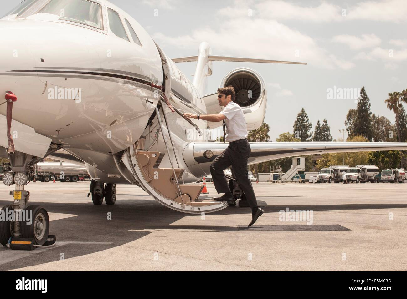Male private jet pilot boarding plane at airport - Stock Image