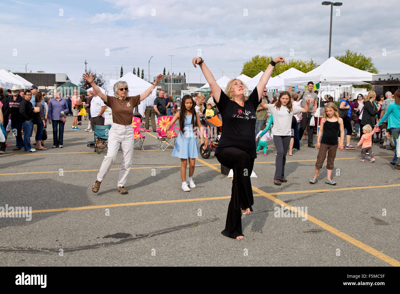 Nia instructor teaching 'movements' at South Anchorage Farmers Market. - Stock Image