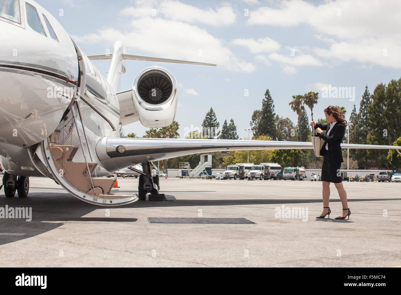 Female businesswoman preparing to board private jet at airport - Stock Image