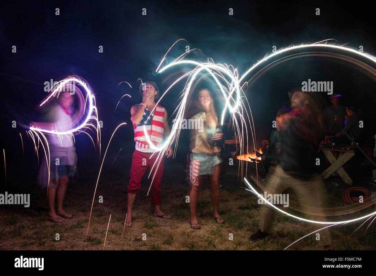Four adult friends celebrating with sparklers in darkness on Independence Day, USA - Stock Image