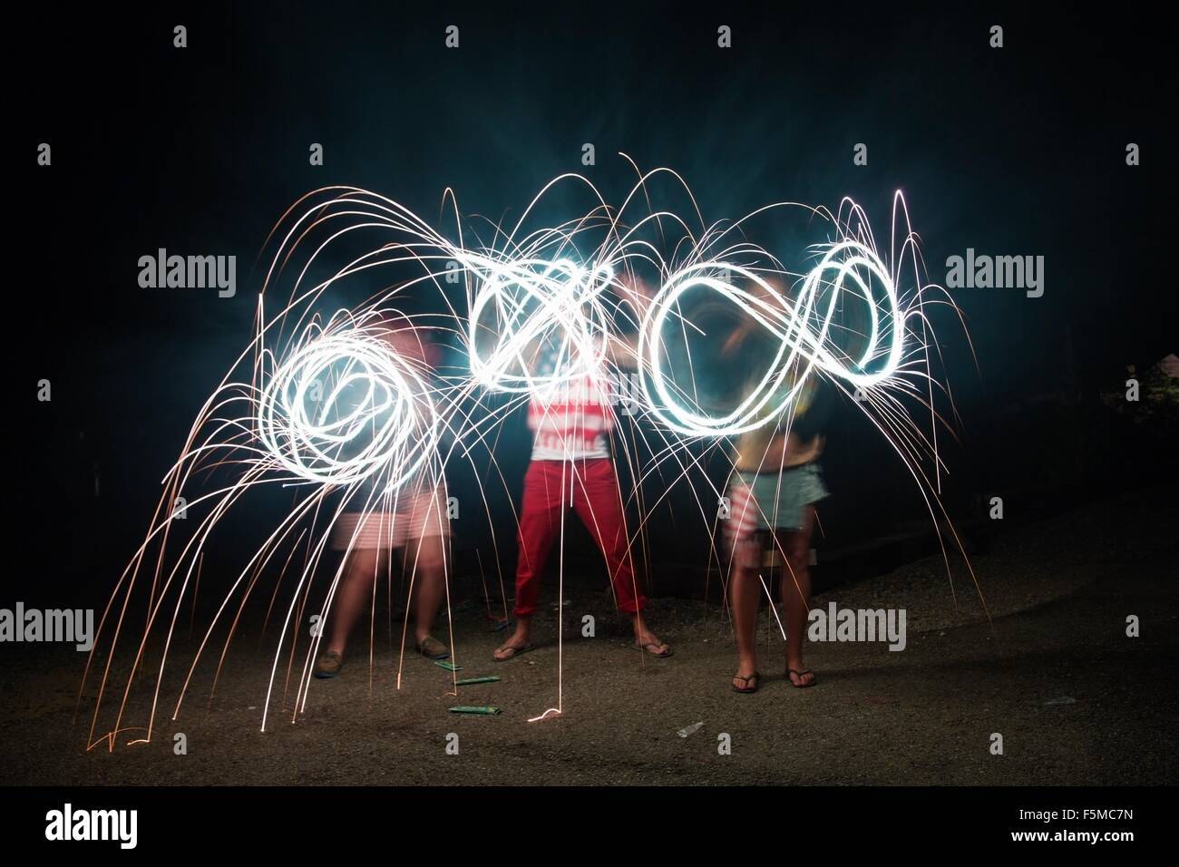 Four adult friends making sparkler patterns in darkness on Independence Day, USA Stock Photo