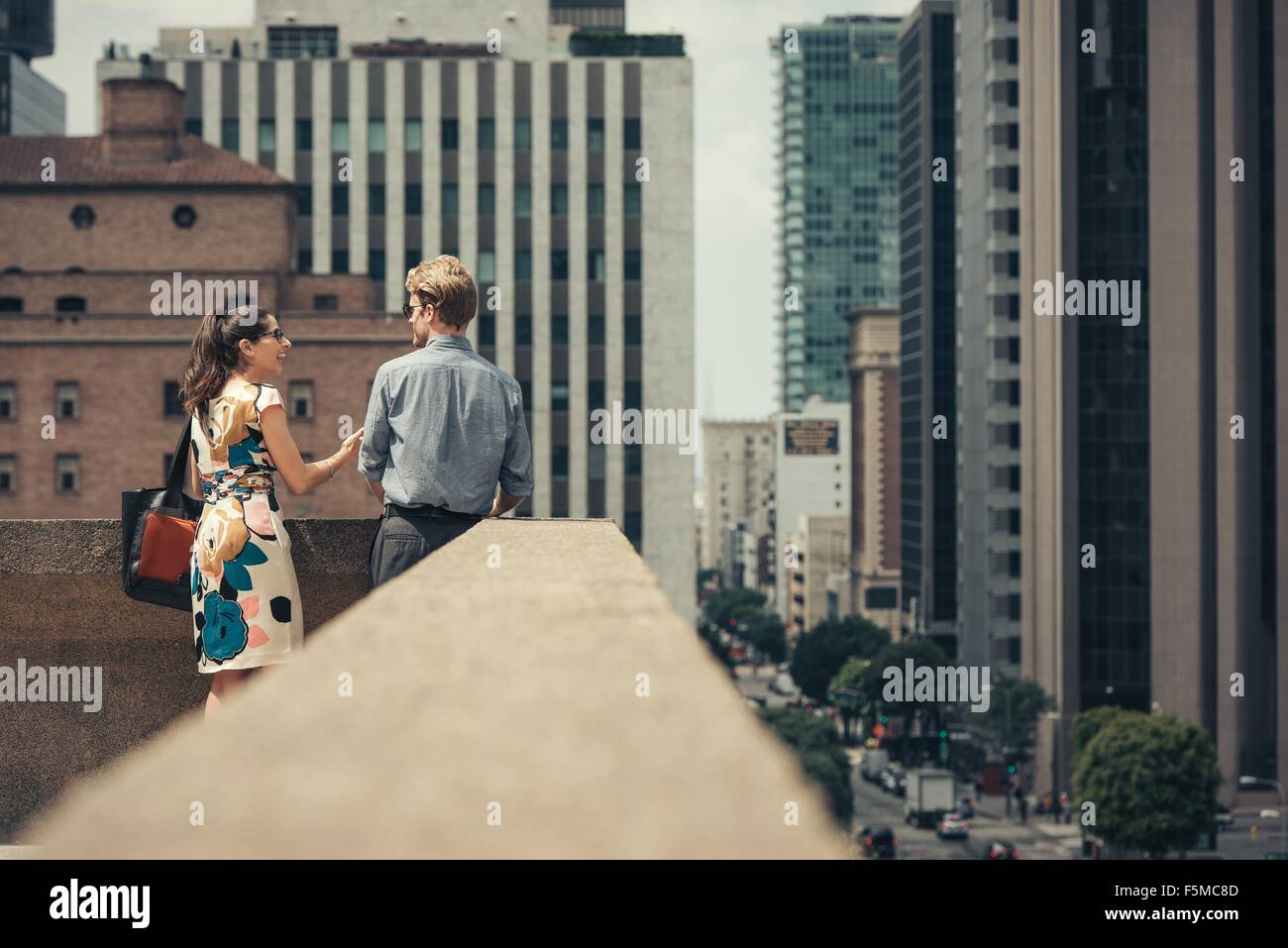 Businessman and woman talking on rooftop, Los Angeles, USA - Stock Image