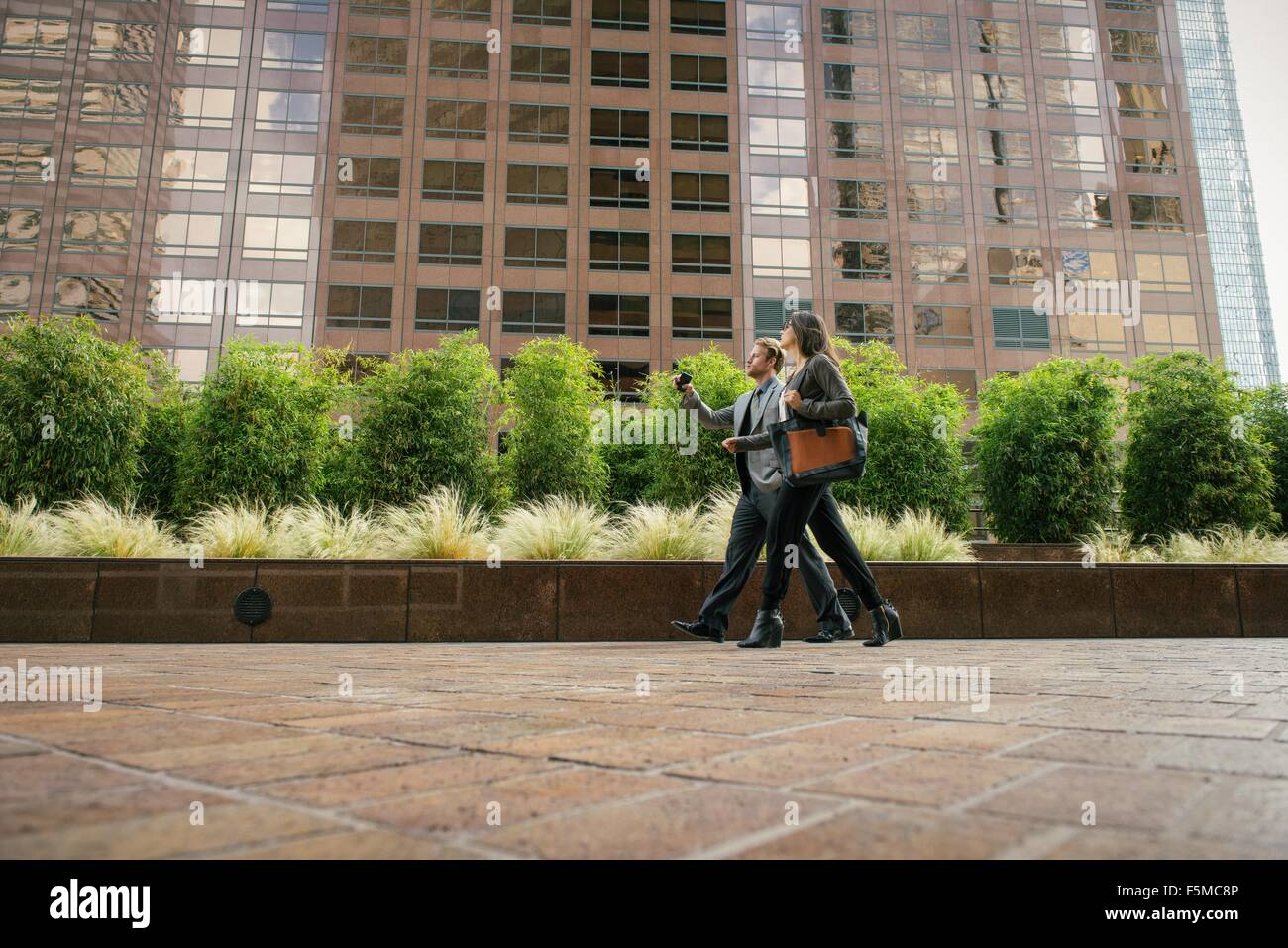 Businessman and woman walking outside office buildings - Stock Image