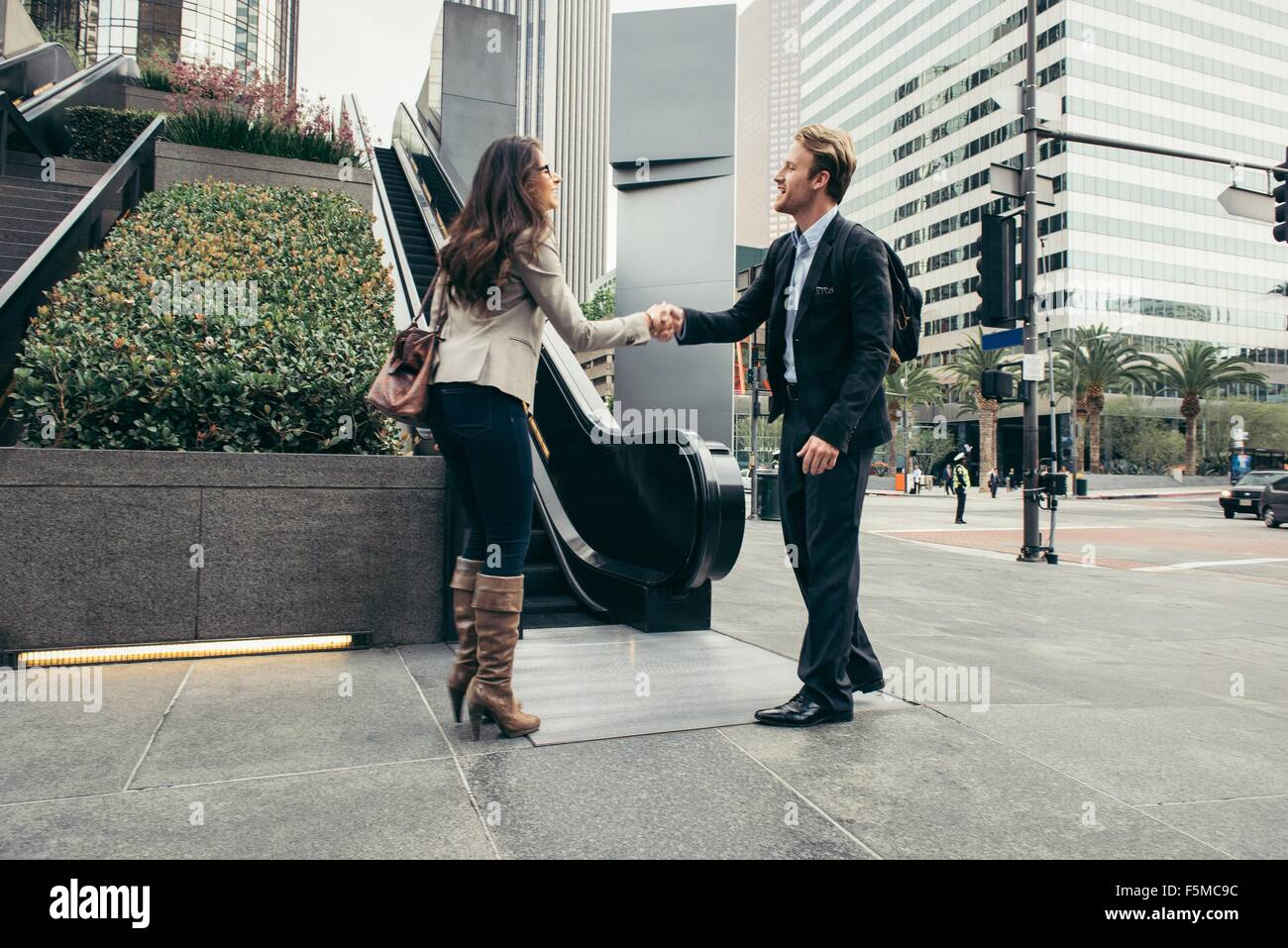 Businessman and woman shaking hands in city - Stock Image