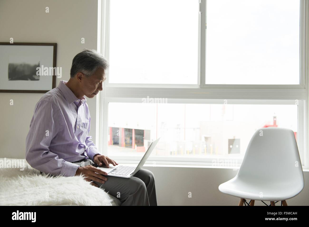 Side view of mature man sitting on edge of bed using laptop - Stock Image