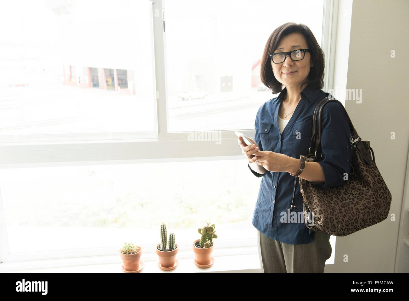 Mature woman standing in front of window holding smartphone looking at camera smiling - Stock Image
