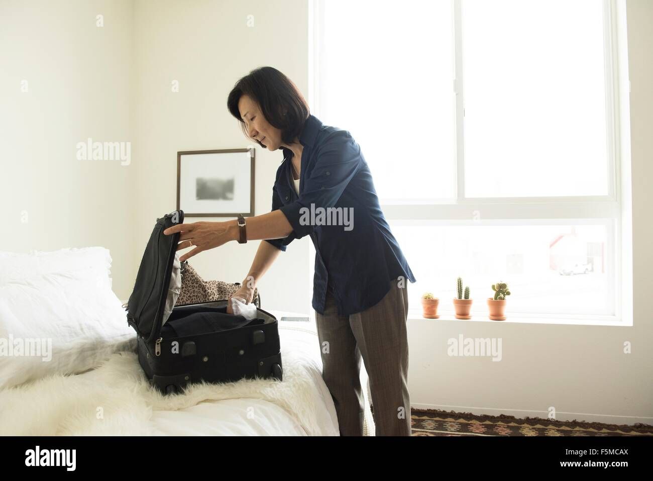 Mature woman standing in hotel room packing suitcase - Stock Image