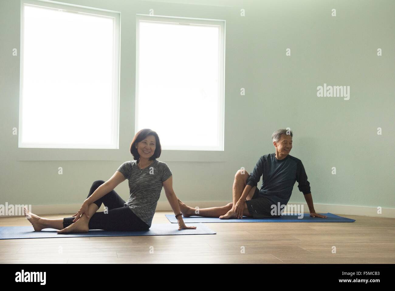 Mature couple sitting on yoga mat leaning on hand, legs crossed looking away smiling Stock Photo