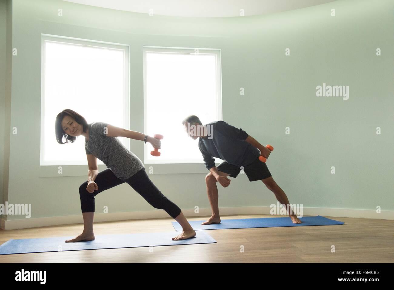 Mature couple on yoga mats exercising using dumbbells - Stock Image
