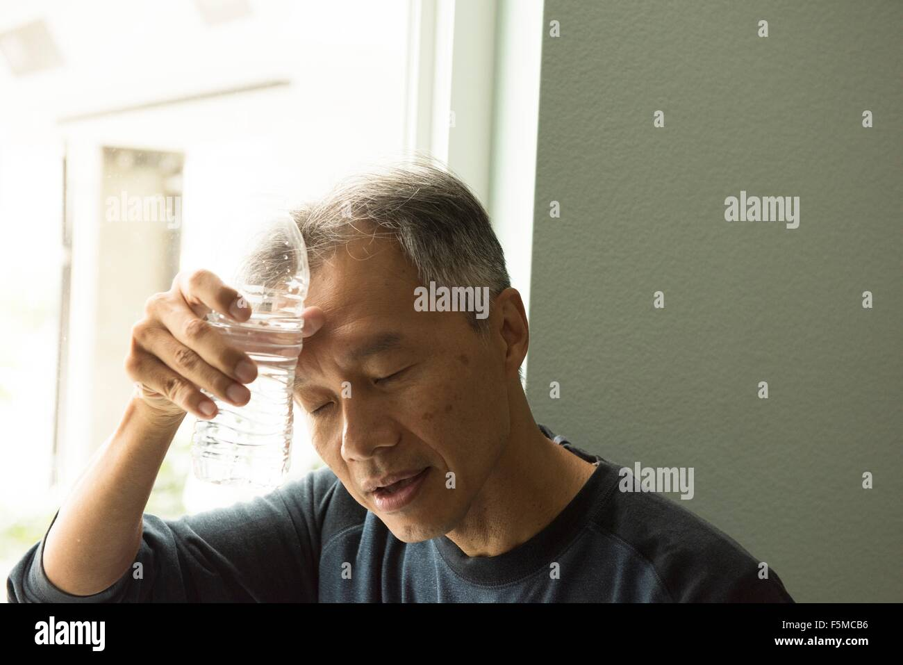 Mature man holding bottle of water to forehead eyes closed - Stock Image
