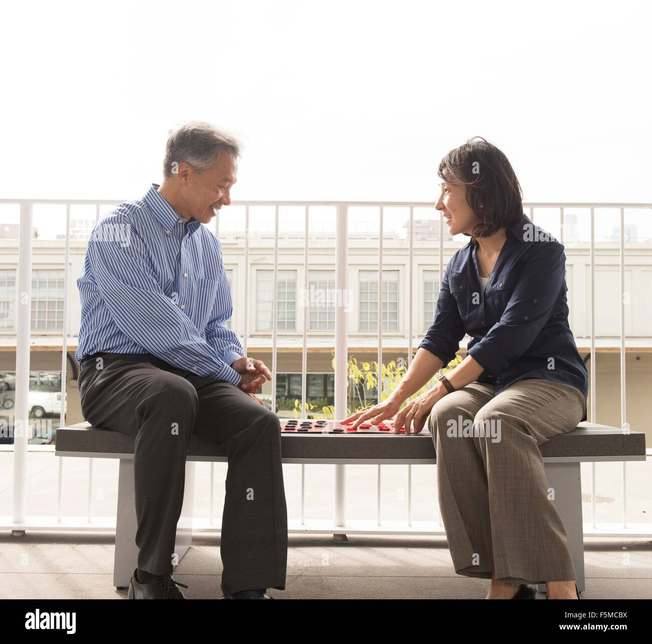 Mature couple sitting on bench face to face playing draughts - Stock Image