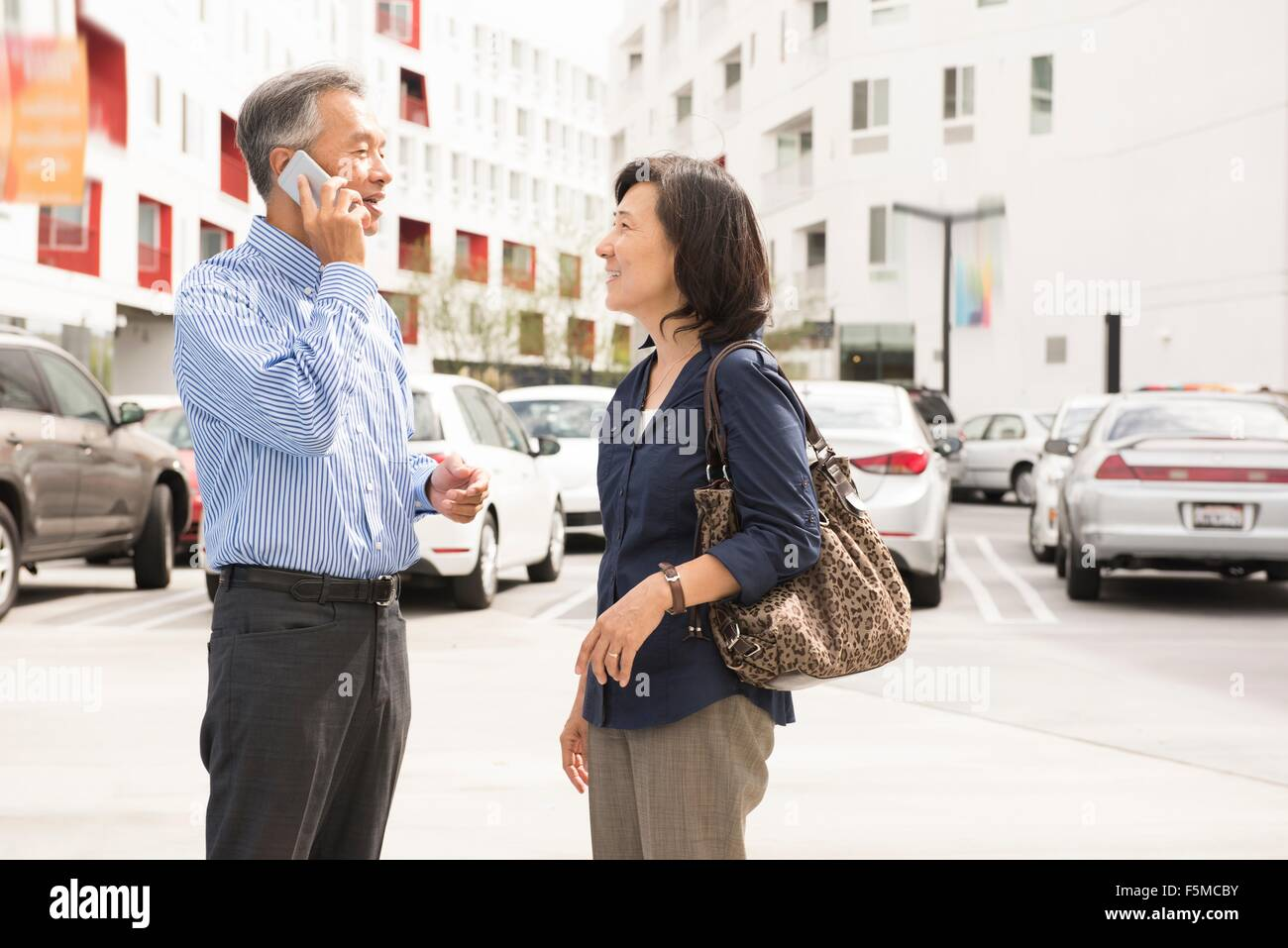 Side view of mature couple standing in parking lot face to face using cellular phone Stock Photo