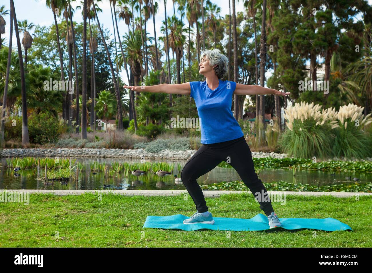 Mature woman doing yoga in park Stock Photo