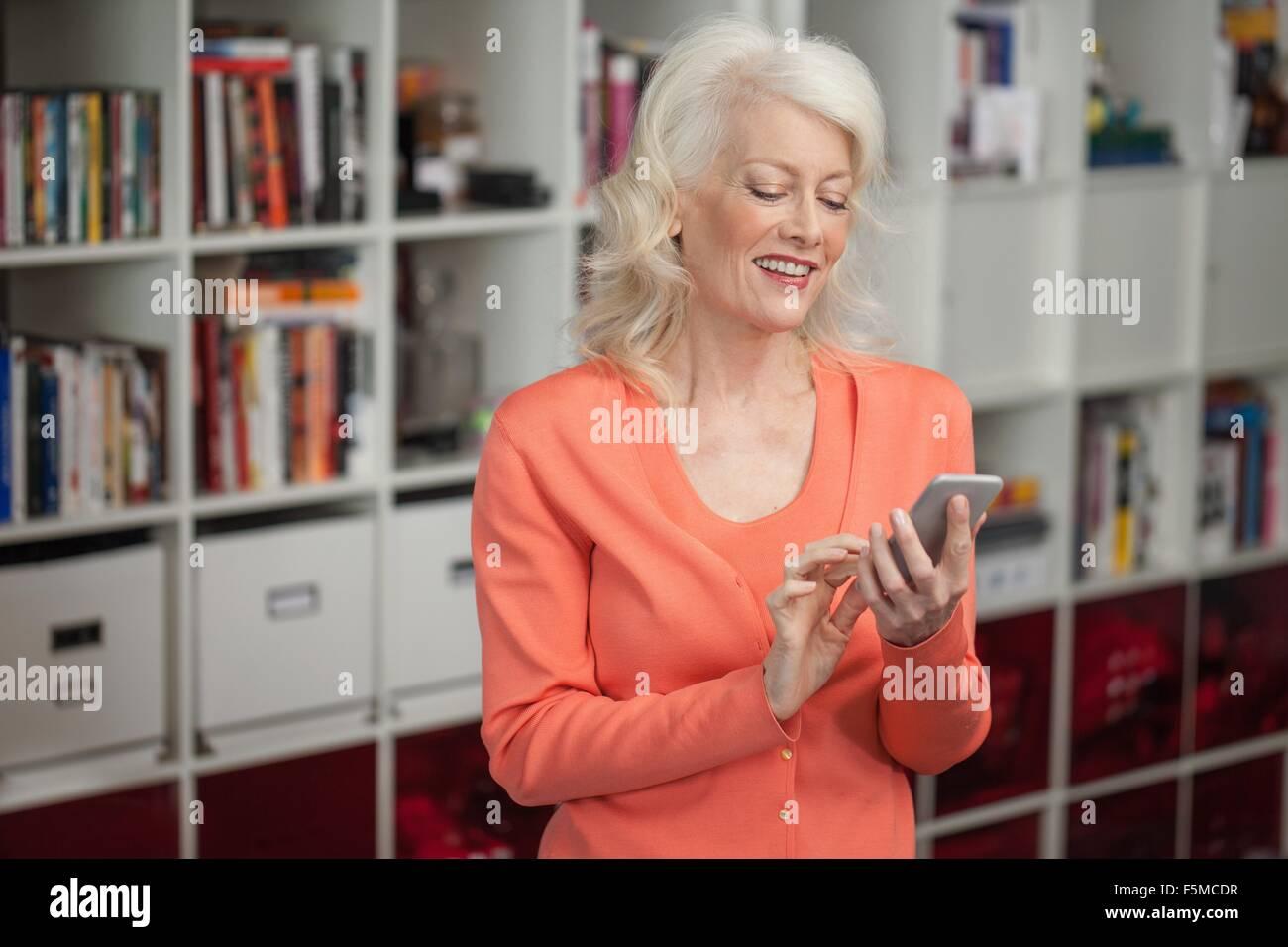 Mature woman using smartphone, indoors - Stock Image