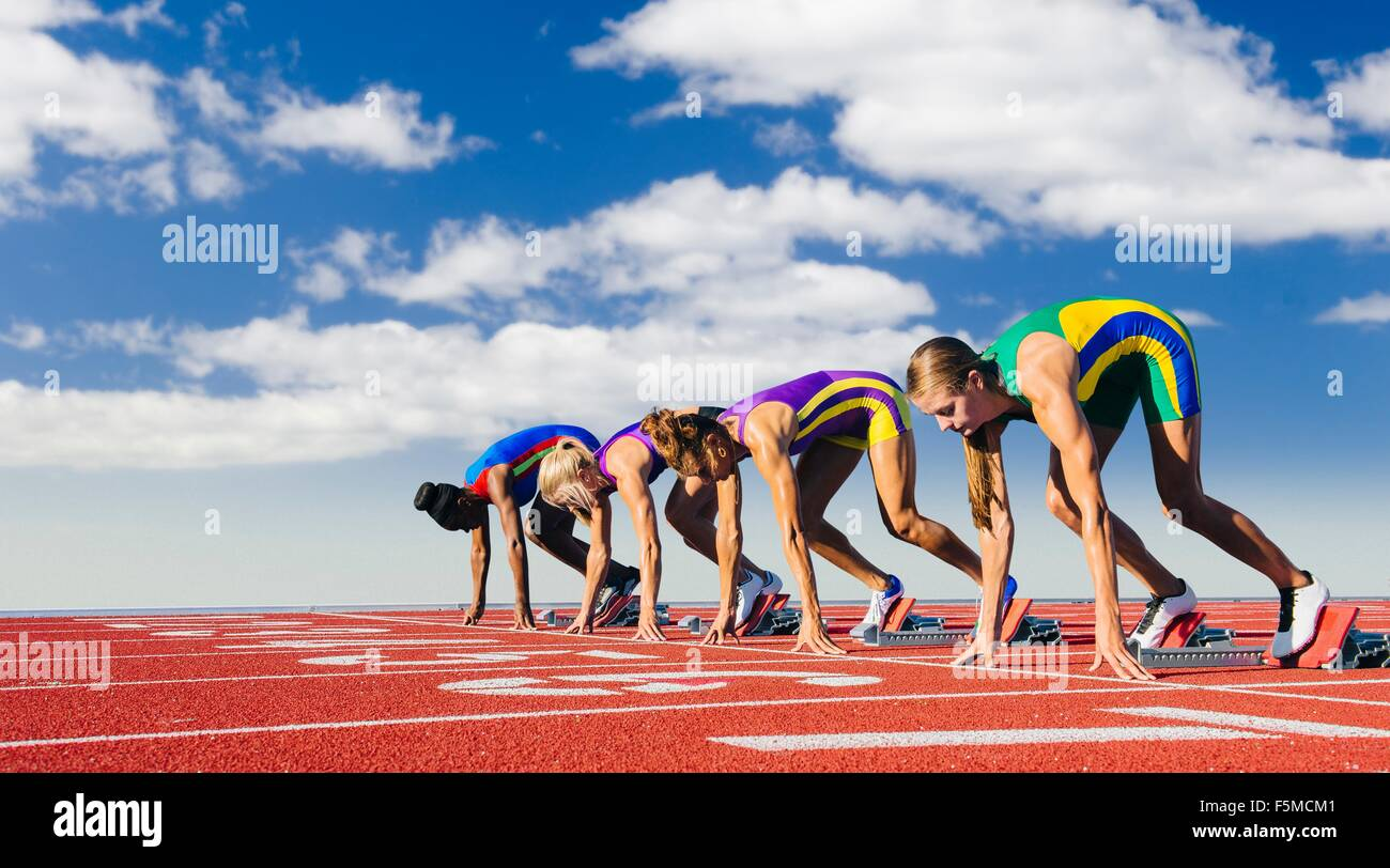 Four female athletes on starting blocks, about to start race - Stock Image
