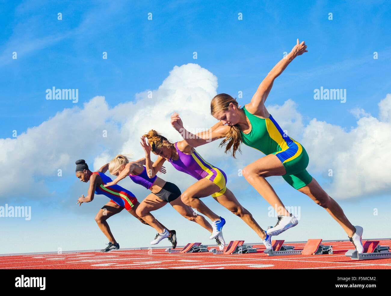 Four female athletes on athletics track, starting race - Stock Image