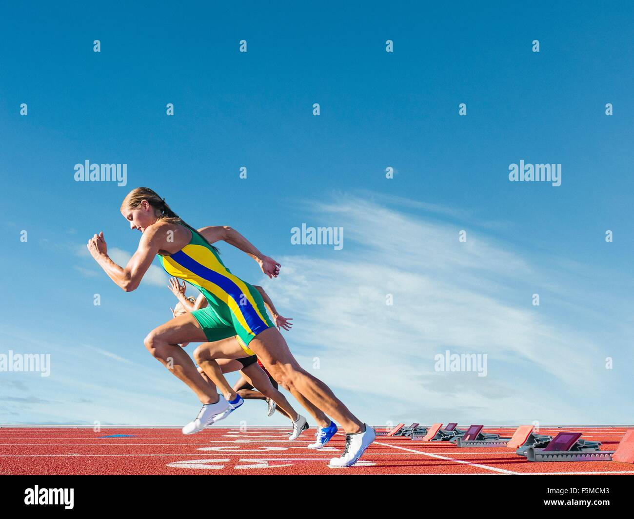 Three female athletes on athletics track, racing - Stock Image