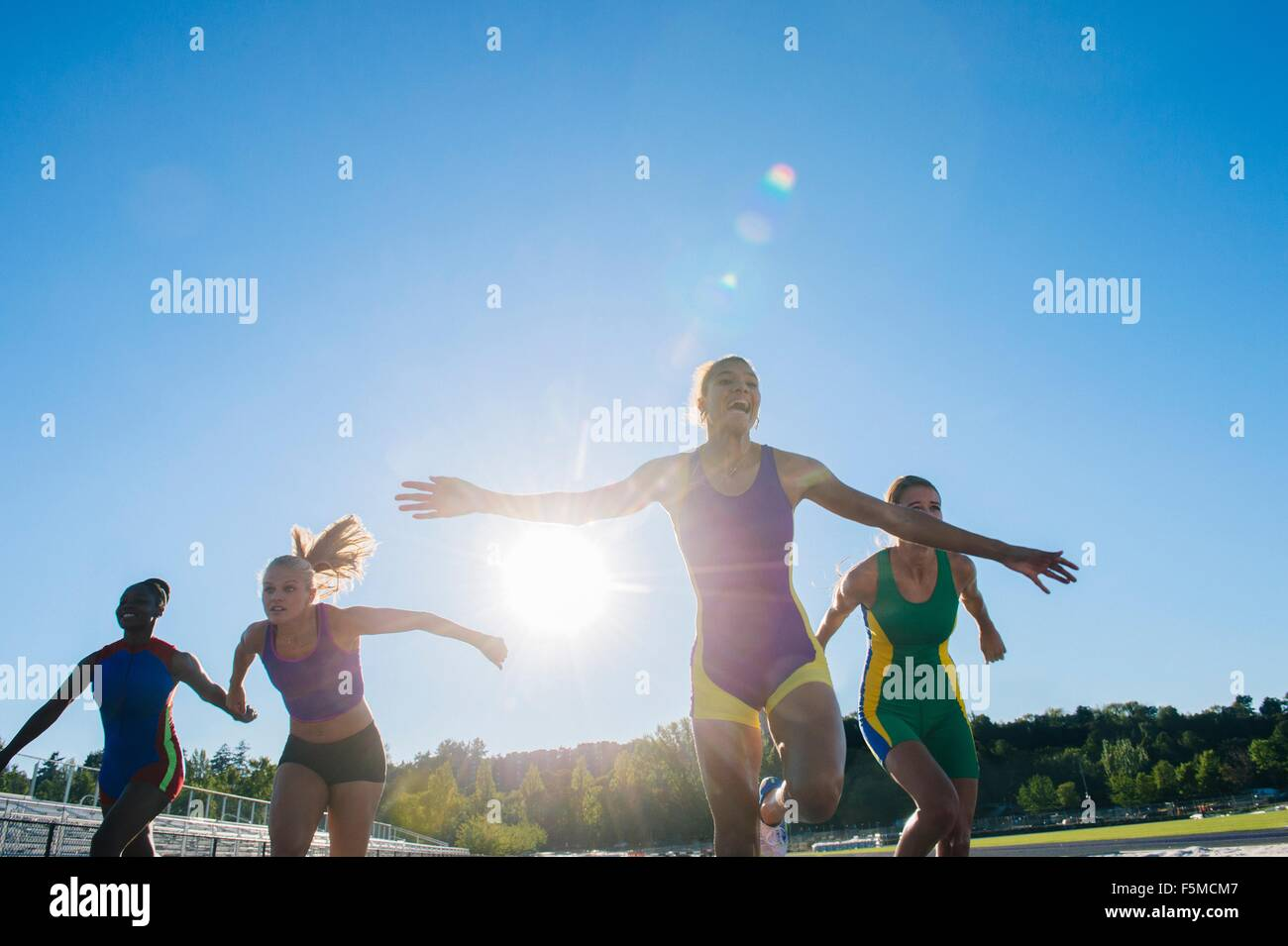 Four female athletes on athletics track, coming to end of race - Stock Image