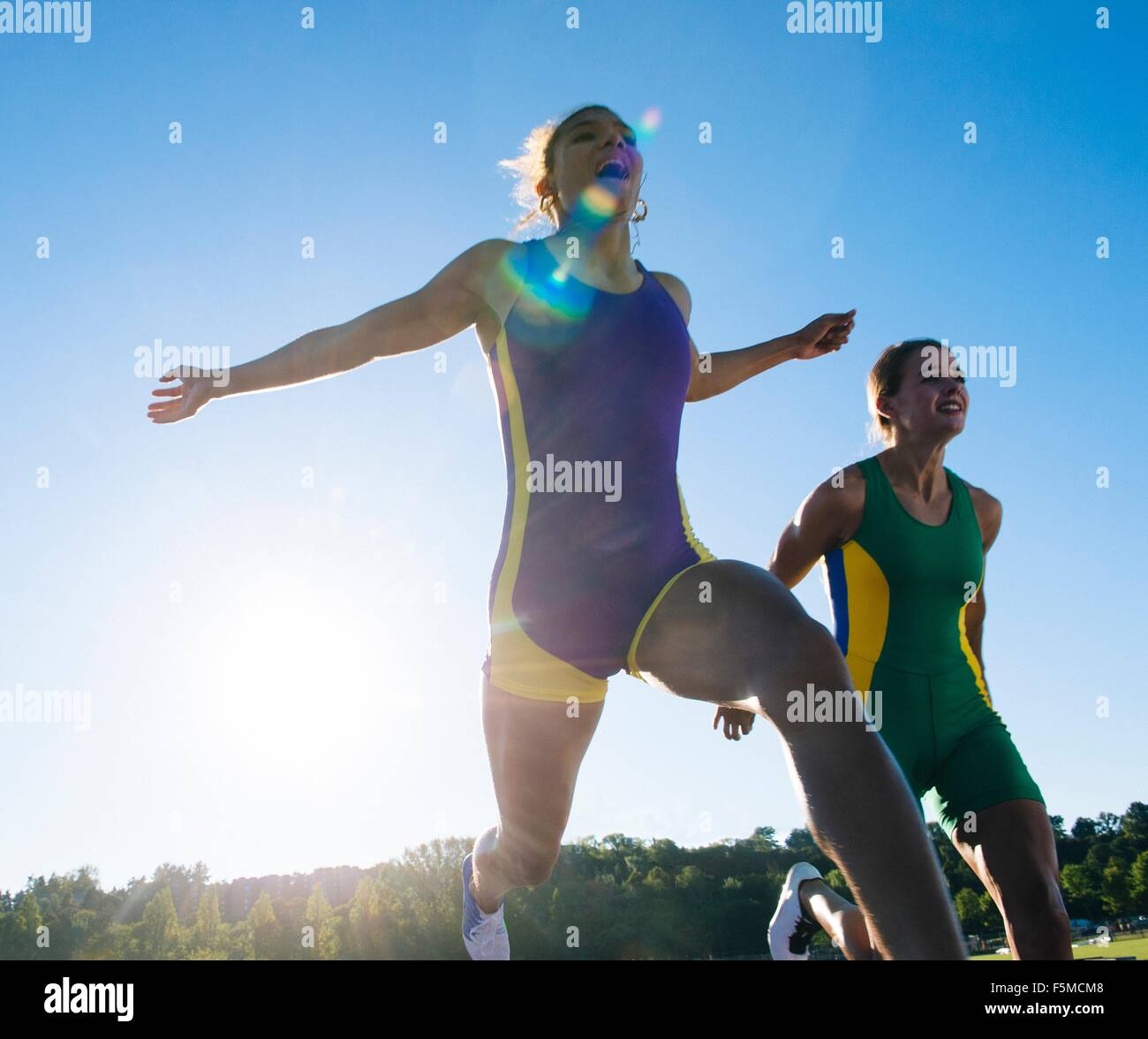 Two female athletes on athletics track, at end of race - Stock Image