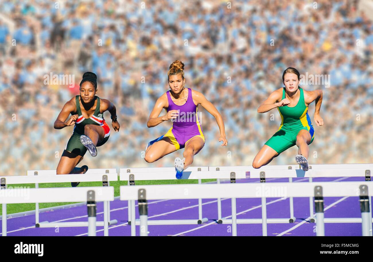 Runners jumping over hurdle on track - Stock Image