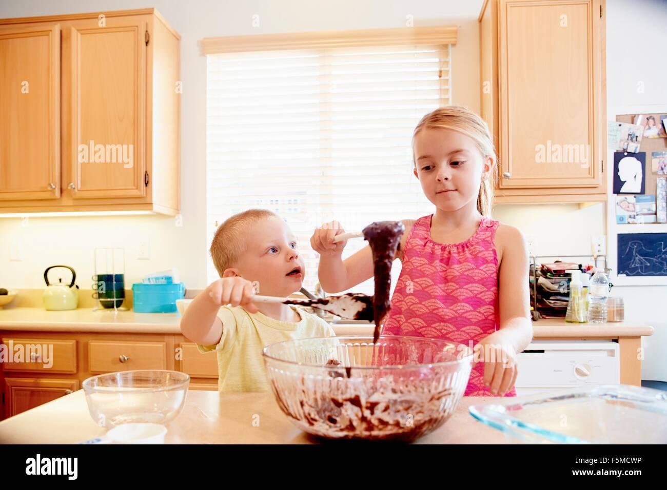 Siblings melting chocolate in mixing bowl - Stock Image
