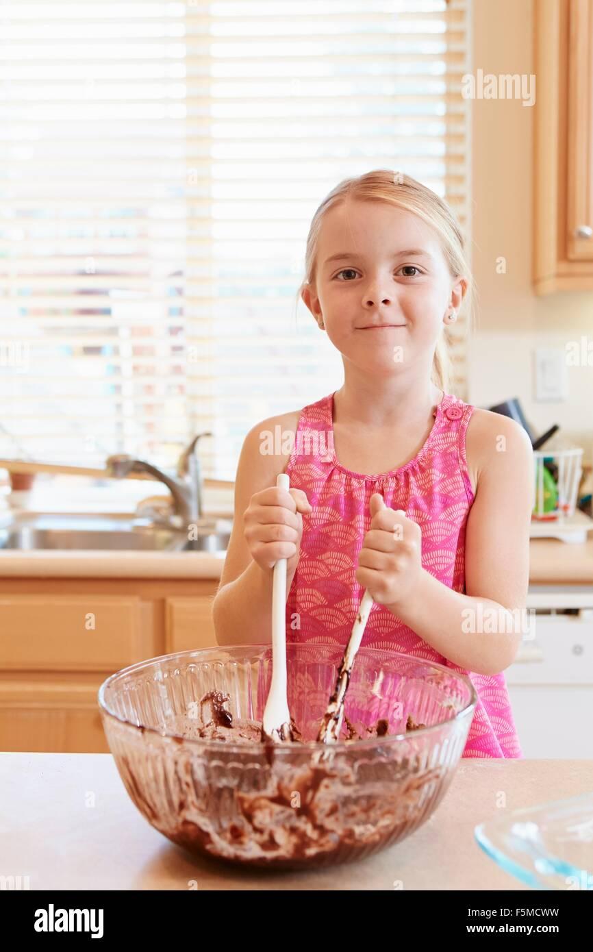 Girl melting chocolate in mixing bowl - Stock Image