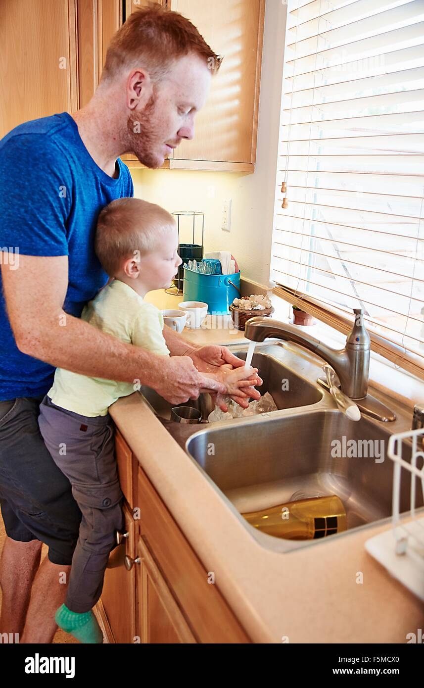 Father washing son's hands in kitchen sink - Stock Image
