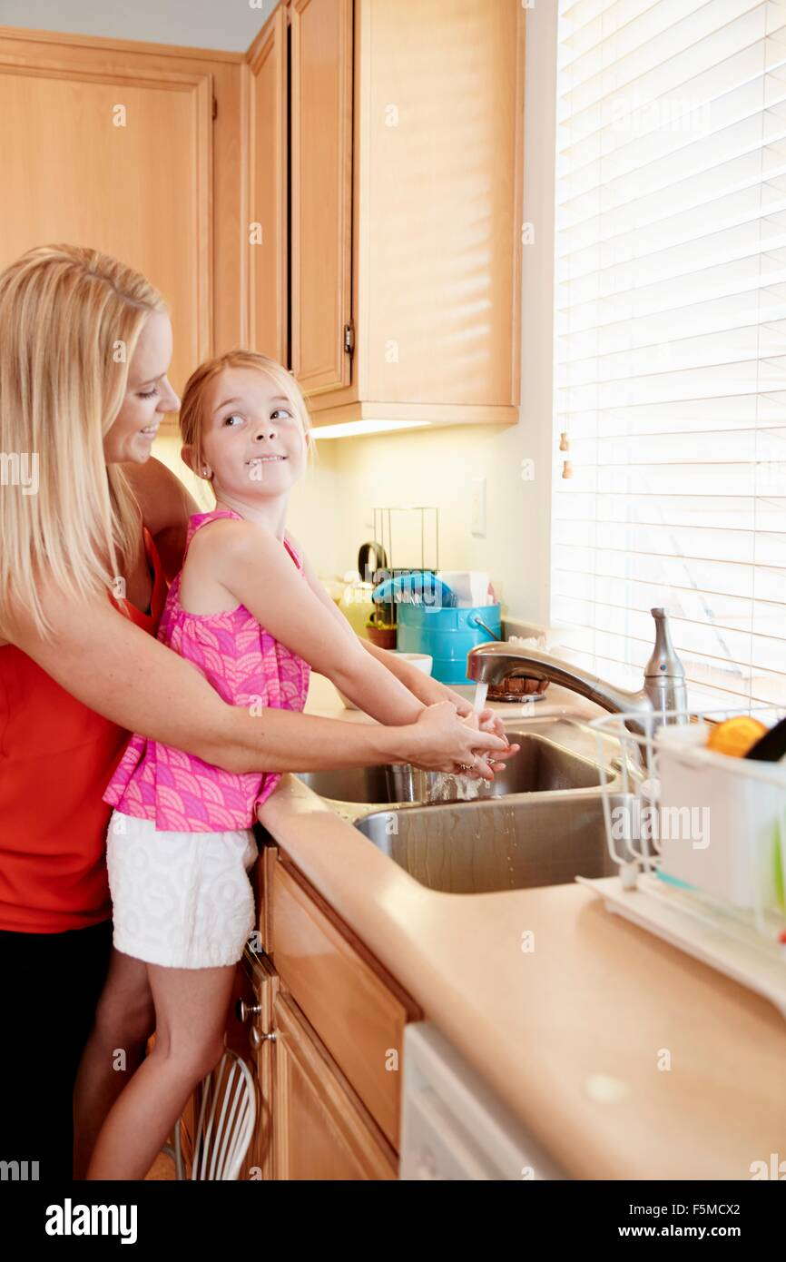 Mother washing daughter's hands in kitchen sink - Stock Image