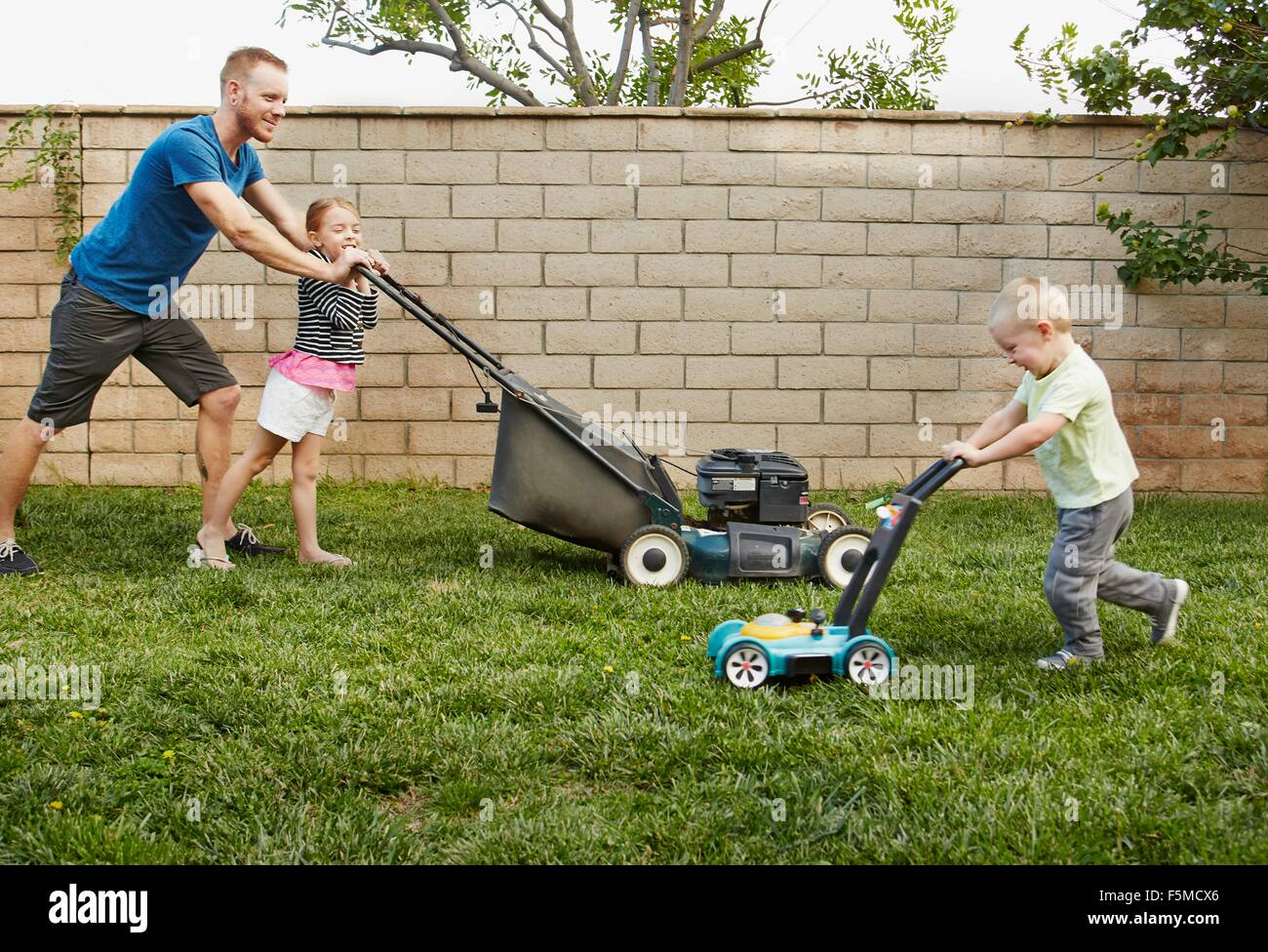 [Image: family-mowing-lawn-in-backyard-F5MCX6.jpg]