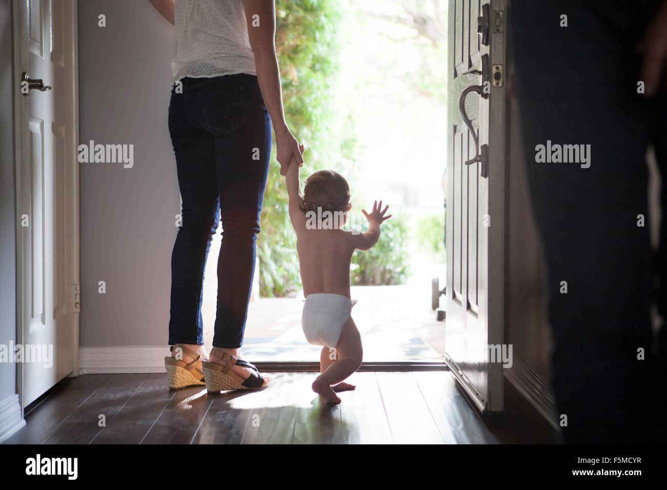 Rear view of mother holding baby boys hands standing at open front door - Stock Image