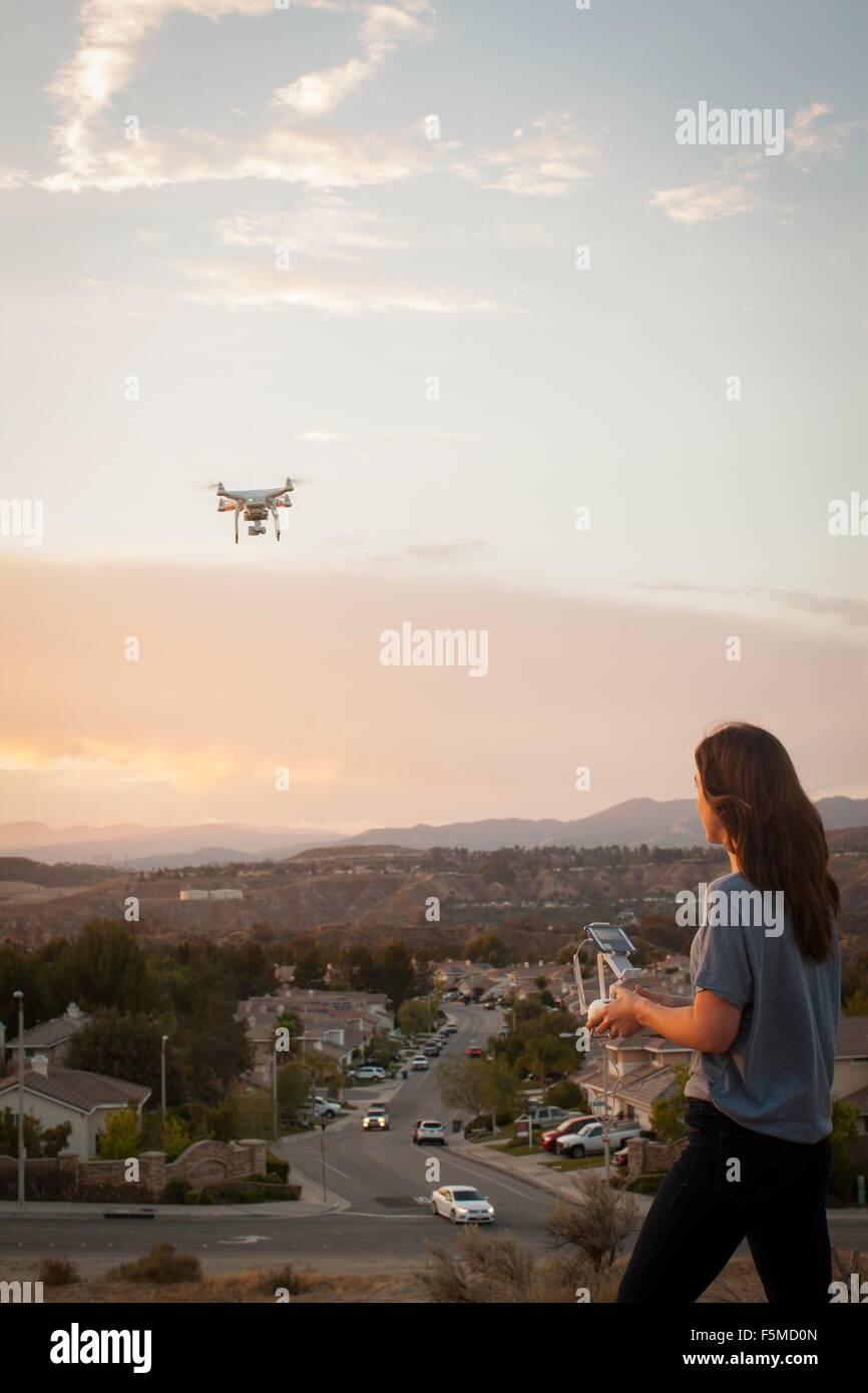 Female commercial operator flying drone above housing development, Santa Clarita, California, USA Stock Photo