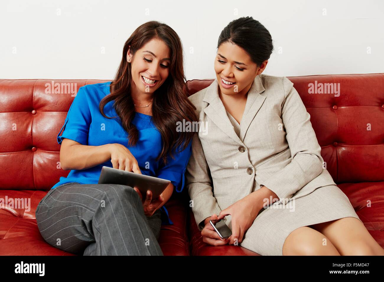 Two businesswomen sitting on sofa, looking at digital tablet - Stock Image