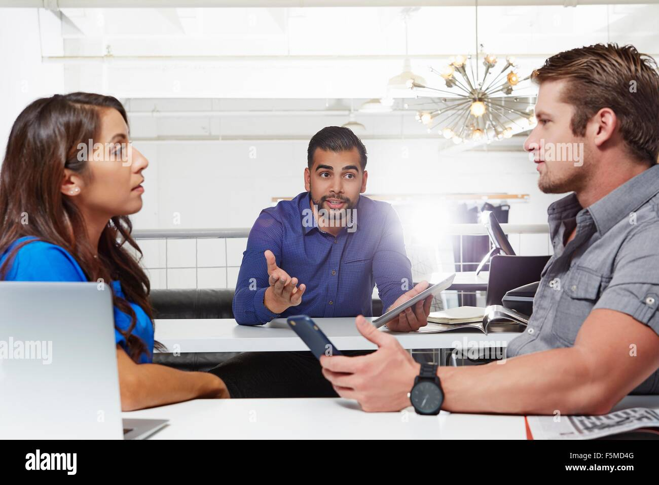 Small group of people having business meeting, male and female colleagues having disagreement - Stock Image