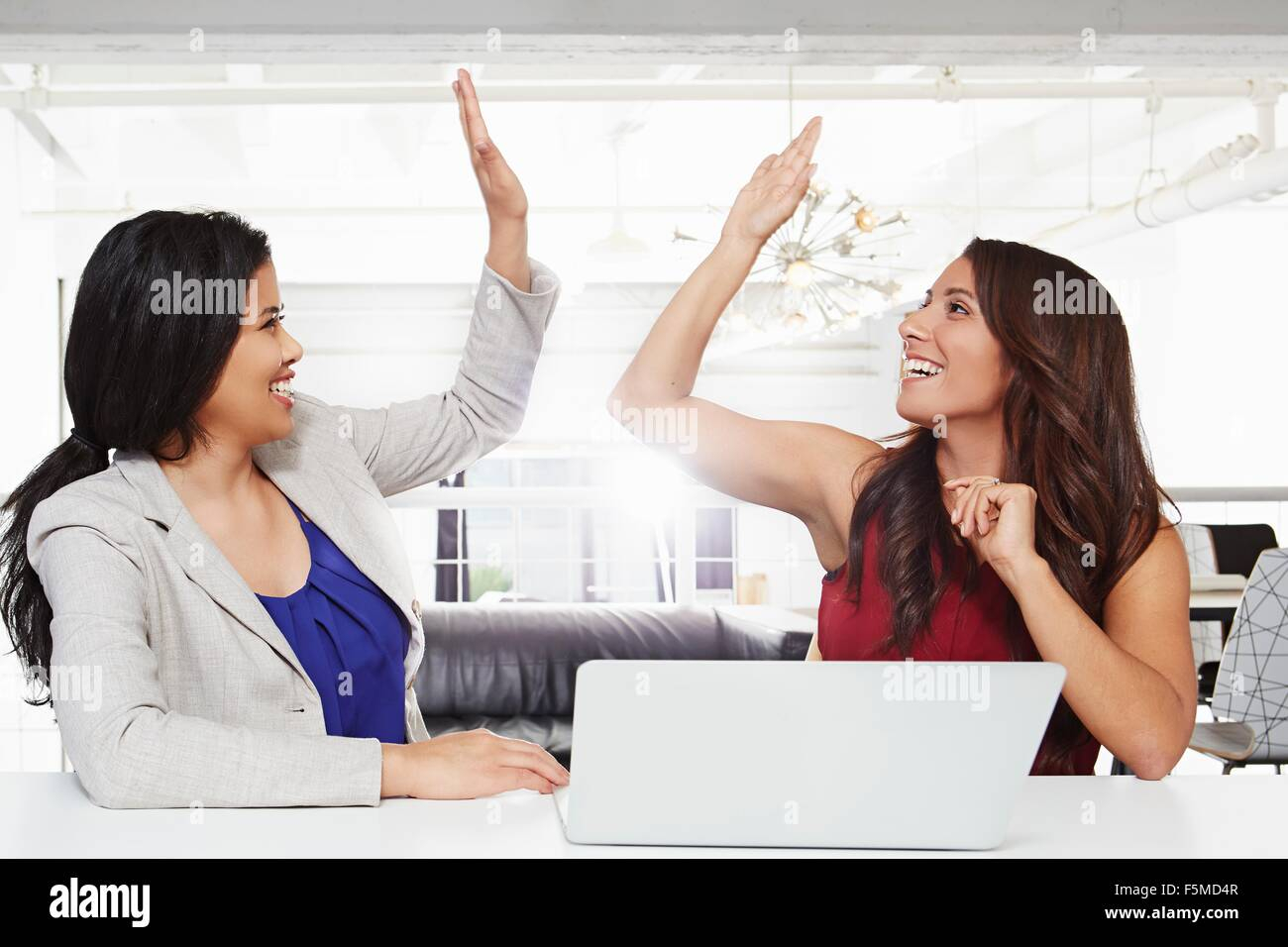 Two businesswomen sitting at desk, giving high five - Stock Image