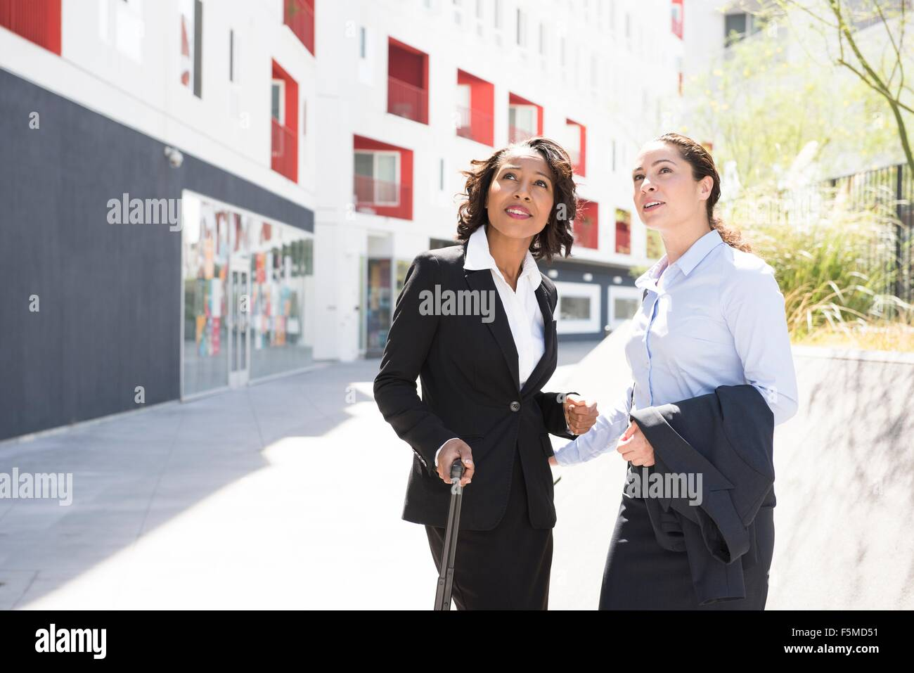 Two businesswomen standing together in street - Stock Image