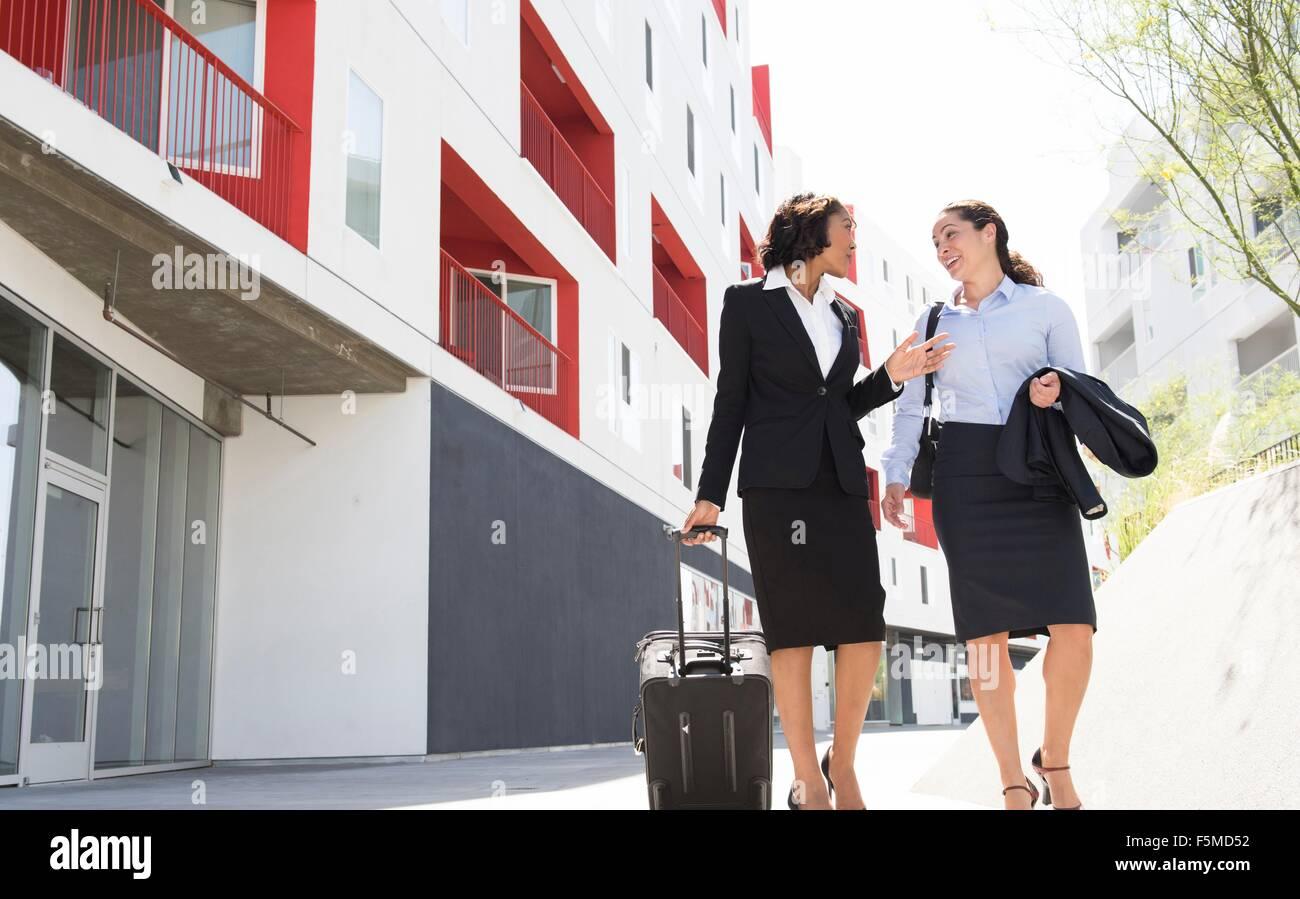 Two businesswomen walking along street, pulling suitcase - Stock Image