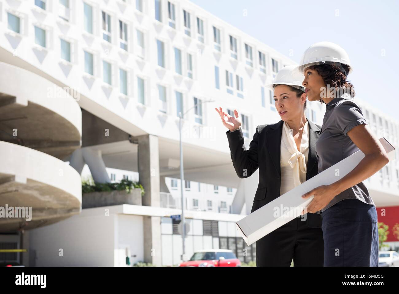 Two businesswomen, wearing hard hats, carrying plans Stock Photo