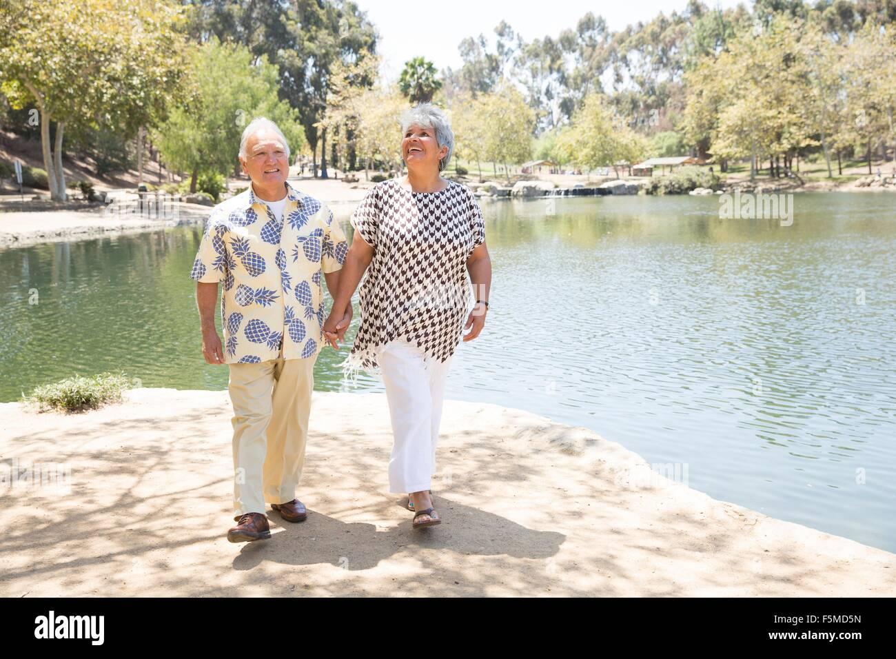 Senior couple walking hand in hand beside lake - Stock Image